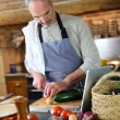 Mature man in kitchen reading recipe on tablet — Stock Photo