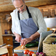 Mature man in kitchen reading recipe on tablet — Stock Photo #35321937