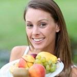 Girl holding fresh fruits — Stock Photo #35324379