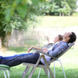 Couple relaxing in long chairs — Stock Photo