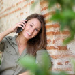 Girl in garden talking on the phone — Stock Photo