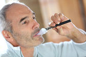 Senior smoker with electronic cigarette — Stock Photo