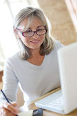Senior woman figuring out income tax — Stock Photo