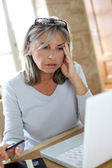 Senior woman in front of laptop — Stock Photo