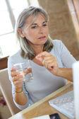 Woman reading medication instructions on internet — Stock Photo