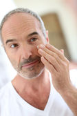 Mature man applying cosmetics — Stock Photo