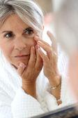 Vrouw toepassing anti-rimpels crème — Stockfoto
