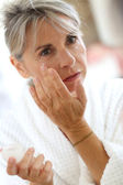 Woman applying anti-wrinkles cream — Stock Photo