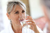 Senior woman drinking water — Stock Photo