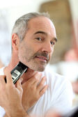 Senior man shaving beard — Stock Photo