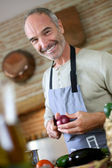 Mature handsome man cooking — Stock Photo