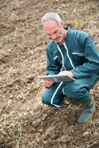 Farmer in field using digital tablet — Stock Photo