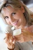 Senior woman eating yoghurt — Stock Photo