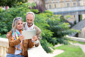 Senior tourists looking for information on tablet — Stock Photo