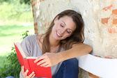 Girl reading book outside — Stock Photo