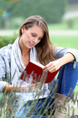 Woman reading book in nature — Stock Photo