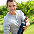 Winegrower presenting wine bottles — Stock Photo