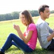 Couple in field playing with smartphone — Stock Photo
