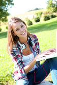 Girl sitting against tree with laptop — Stock Photo
