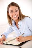 Saleswoman writing notes on agenda — Stock Photo