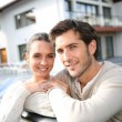 Cheerful couple in front of new home — Stock Photo