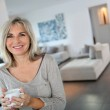 Mature woman at home drinking tea — Stock Photo #36647417