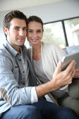 Smiling couple with tablet — Stock Photo