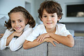 Brother and sister on sofa — Stock Photo