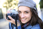 Smiling girl holding camera — Stock Photo