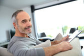 Mature man using tablet — Stock Photo