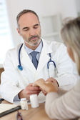 Doctor giving medicine to senior woman — Stock Photo