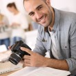 Cheerful reporter with camera — Stock Photo