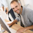 Cheerful man in front of computer — Stock Photo