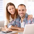 Smiling couple calculating savings — Stock Photo