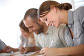 Smiling people filling admission form — Stock Photo