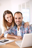 Cheerful couple calculating savings — Stock Photo