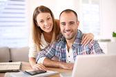 Smiling couple calculating savings — Stock Photo
