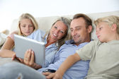 Family in couch websurfing — ストック写真