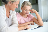 Mother helping girl with homework — Stock Photo