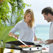 Couple preparing grilled food — Stock Photo #38961535
