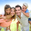Parents giving piggyback ride to kids — Stock Photo #38962171