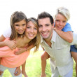 Parents giving piggyback ride to kids — Stock Photo #38962209