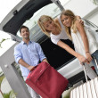 Parents with child putting luggage in car trunk — Stock Photo