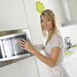 Woman using microwave oven — Stock Photo #38967301