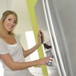 Young woman opening fridge — Stock Photo #38967307