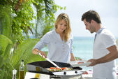 Couple preparing grilled food — Stock Photo