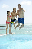 Man with kids jumping in swimming pool — Foto Stock