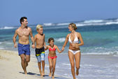 Family running on a beach — Stockfoto