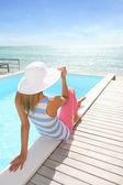 Girl sitting by infinity pool — Stock Photo