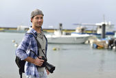 Photographer standing by fishing harbour — Stock Photo